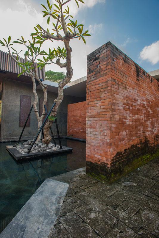 interessante Gestaltung über Farben, Mauerwerk und Pflanze in Kombination mit eingelassenem Teich