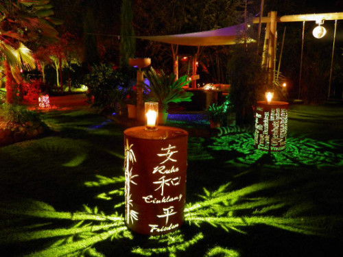 kunstvoll gestaltete und beleuchtete Fässer sorgen für besondere Abendstimmung im Garten